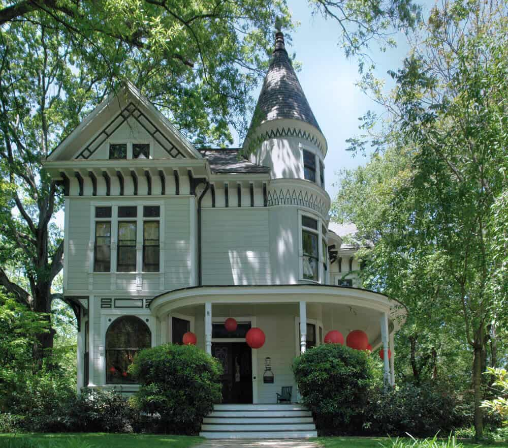 Modest light green Victorian home with large front round porch situated among trees.