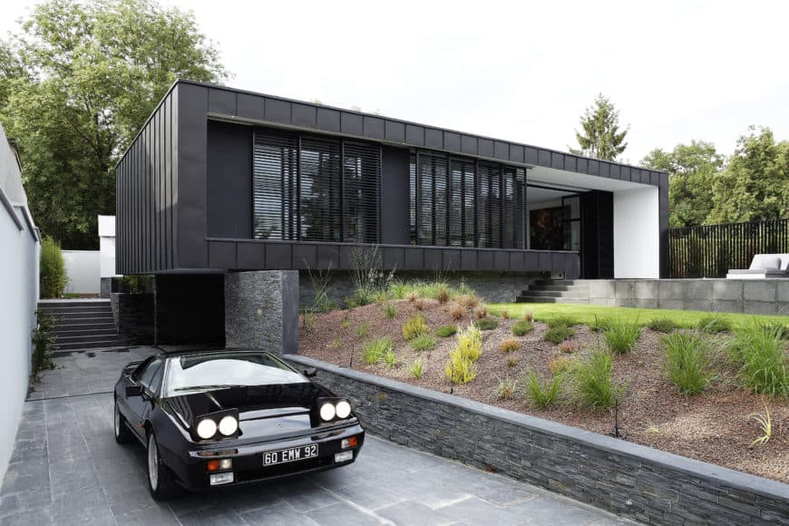 A black modern house with a good-looking driveway leading straight to the home's garage.