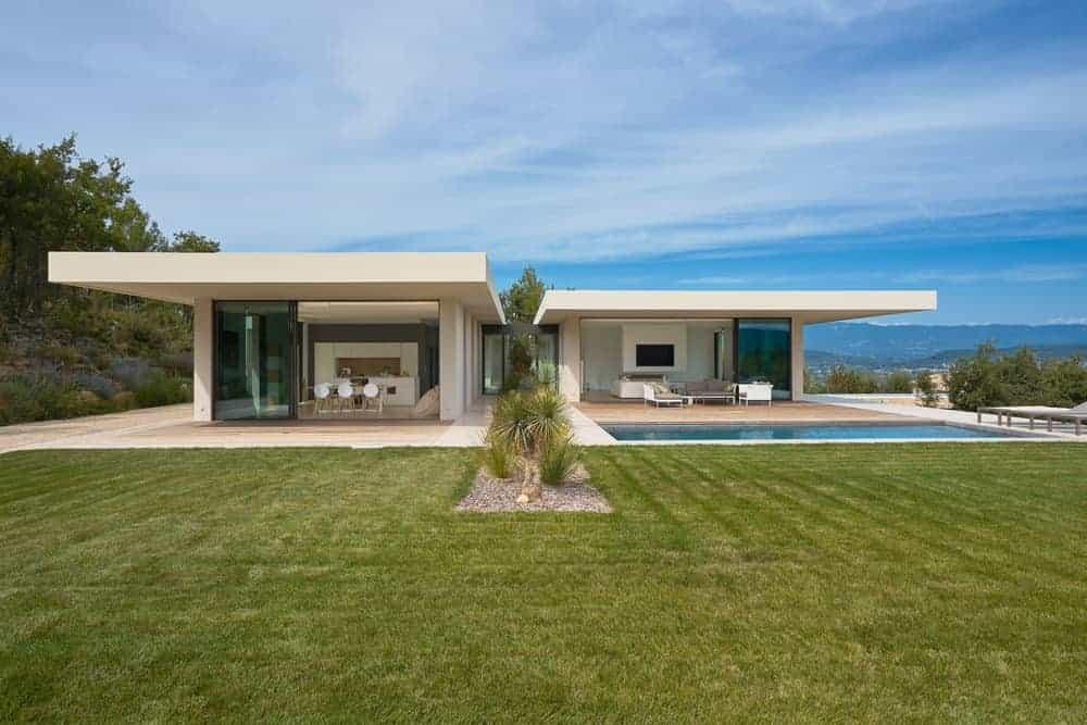 A large white modern house with a sprawling lawn area along with a swimming pool.