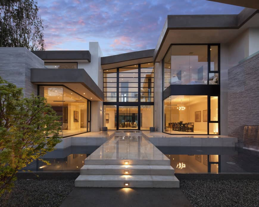 A modern mansion with a stylish exterior design and has a stunning walkway leading to the entry.