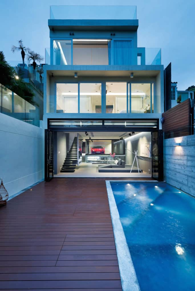 This modern house features an indoor garage and a small deck with a swimming pool on the side.