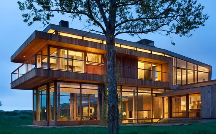 Modern big timber riverside home with warm white lights in its interior.