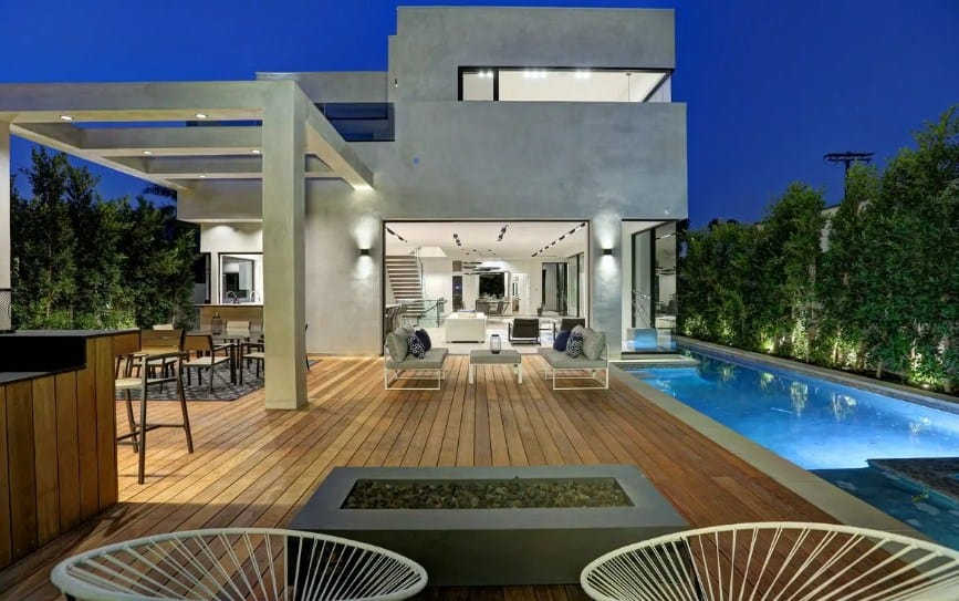 Large modern home with a spacious deck featuring an outdoor kitchen and bar, along with an outdoor dining, an outdoor living and a swimming pool.