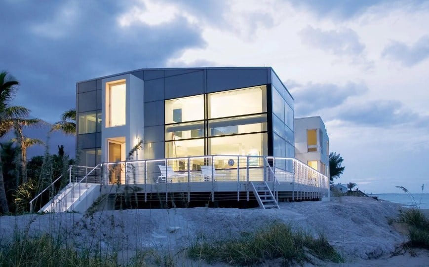 A modern beach house with a gorgeous exterior, along with a long deck overlooking the ocean view.