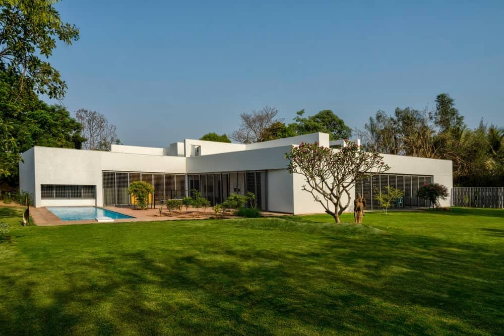 This charming modern home is a wonderful contrast to its lush green landscape. It has light gray exterior walls complemented by large entryways and wide windows that are covered with railings. There is a lovely outdoor area on the side with a pool and a sitting area on terracotta flooring.