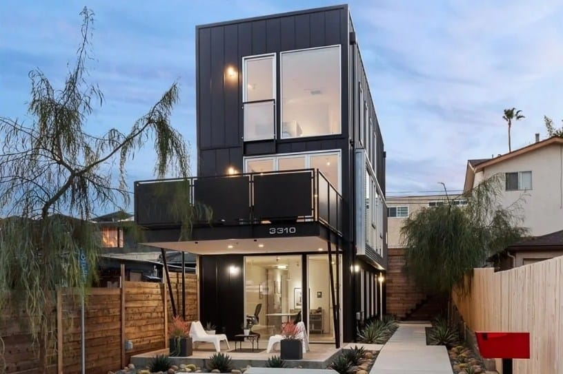 Modern industrial home featuring a black exterior. The home has a nice backyard with a beautiful walkway.