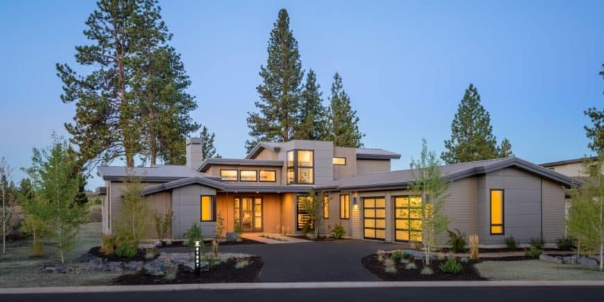 This modern house features a nice driveway and a peaceful backyard.