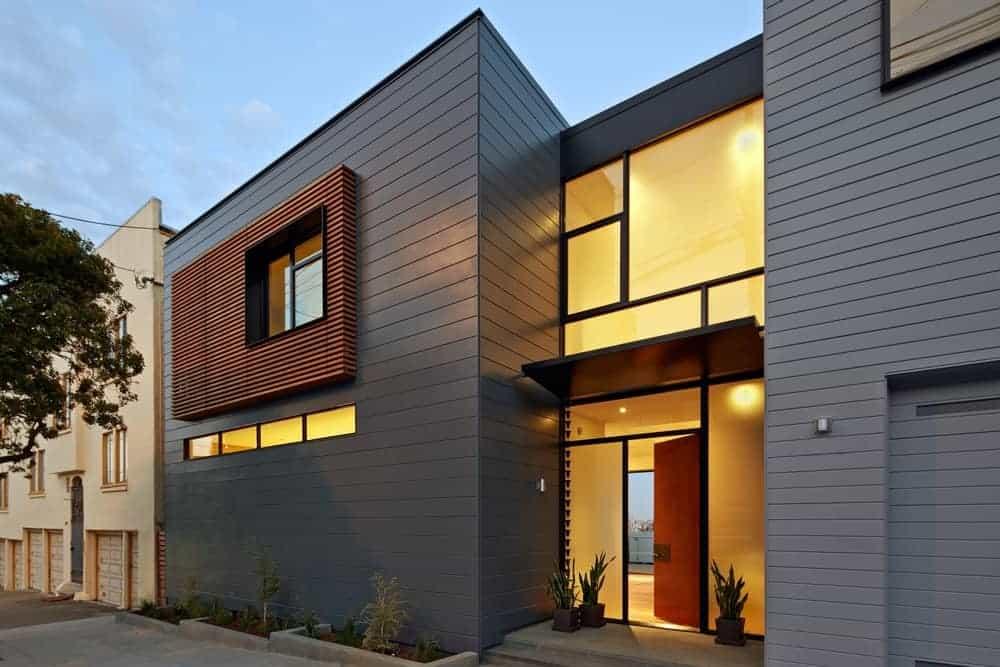 Modern home with a gray exterior and features warm white lights on its interior.