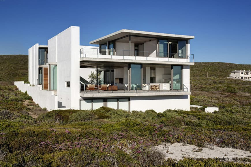 Large white modern home with a nice balcony and terrace offering a stunning view of the surroundings.