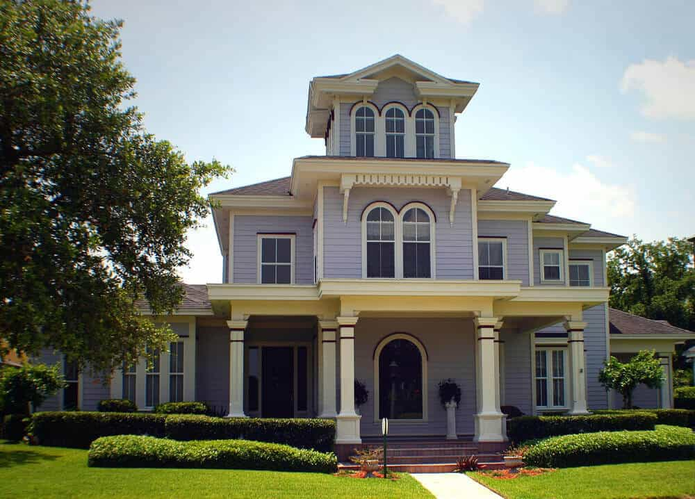 Simply-designed purple and white Victorian home with large front porch and arched windows.