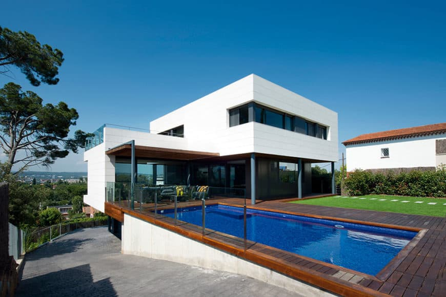 A modern house with a white exterior and a nice backyard. It features a deck along with a swimming pool and a well-maintained lawn area with a walkway.
