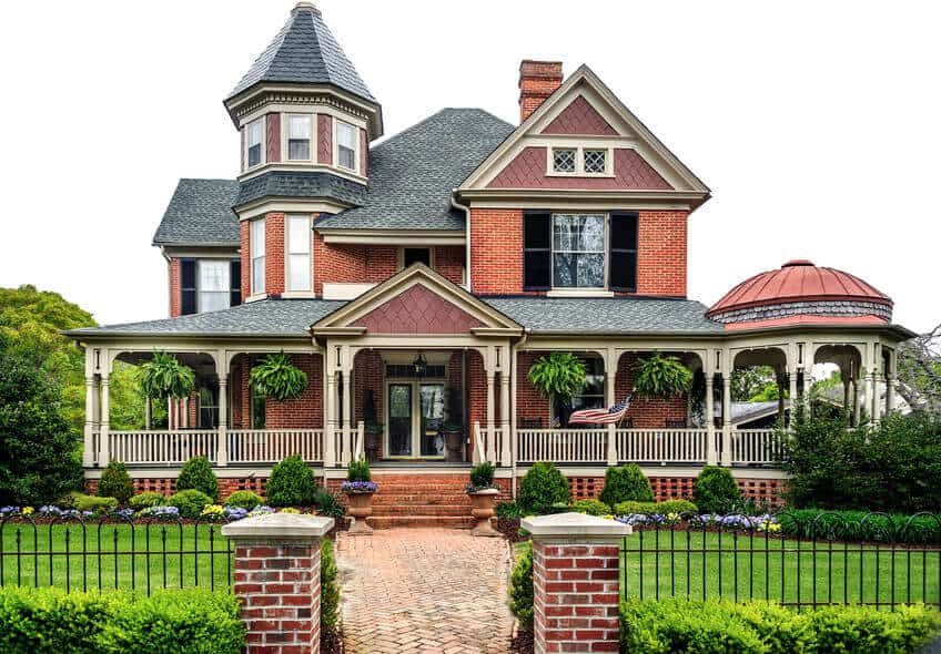 Large red brick with white trim Victorian house with wrap-around veranda and attached gazebo.