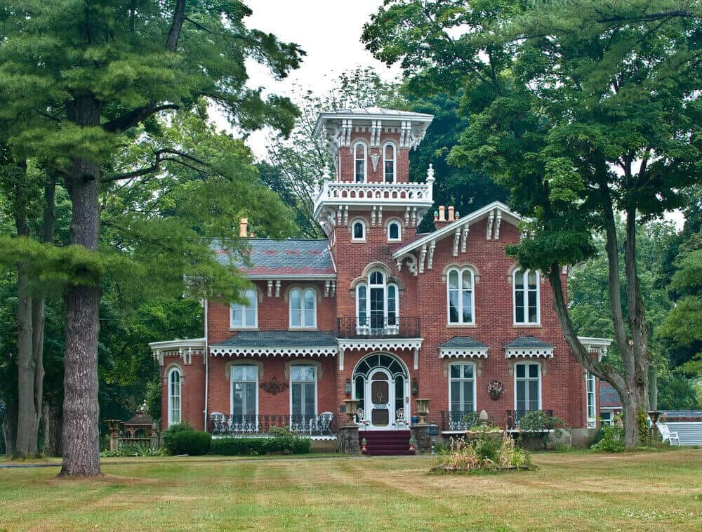 Large red brick Victorian home with central tower among trees on a large property.
