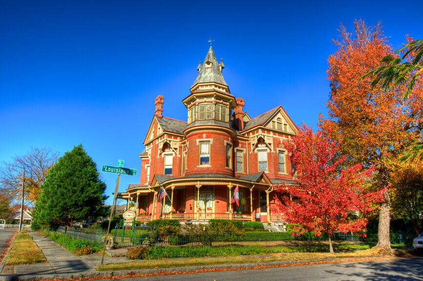 Ornate red brick Victorian mansion on corner lot in Arkansas.