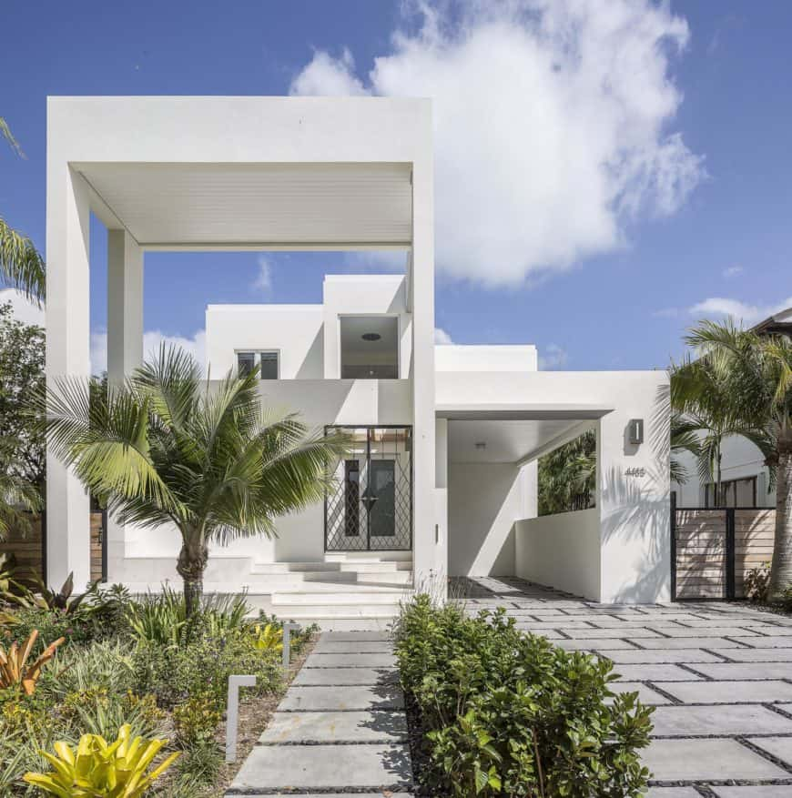 A beautiful white modern house with a gorgeous walkway and a garden area.