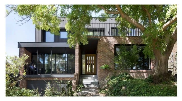 A renovated modern home with a brick exterior and has a nice porch.