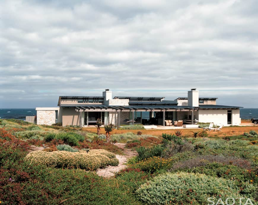 This modern house boasts a beautiful garden area and offers a stunning look of the ocean view.