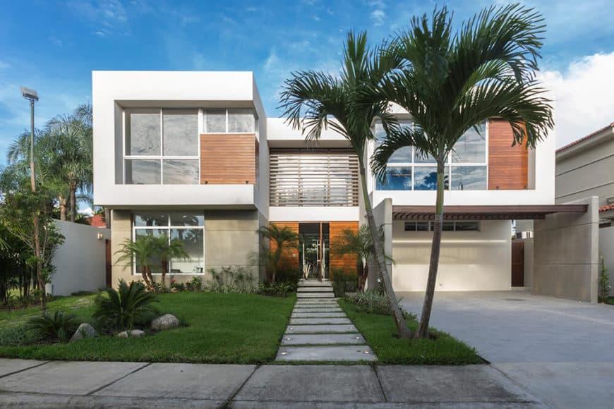 A modern house featuring a wide garage, a beautiful garden and a gorgeous walkway.