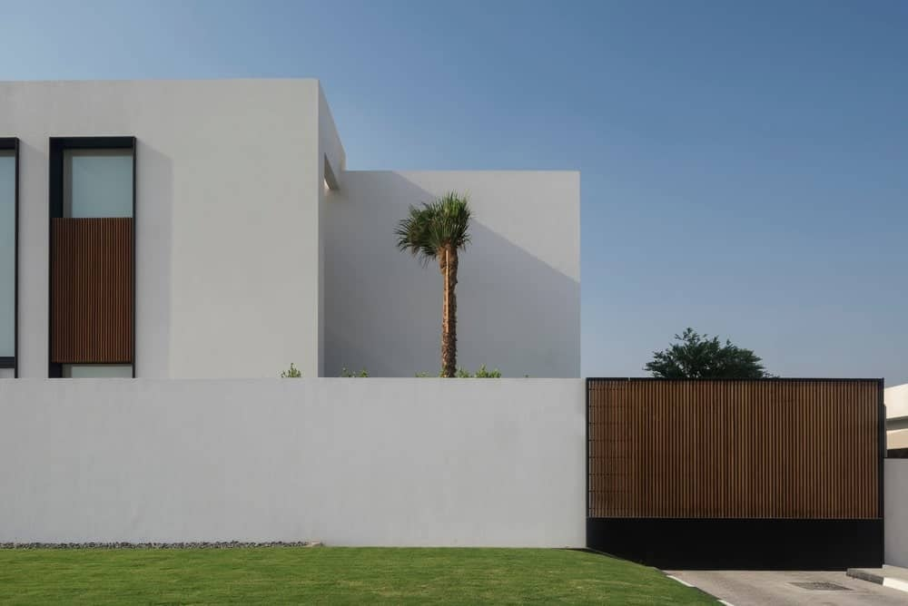 Sleek, modern home with a minimalist design showcasing white walls with subtle wood panels accent. Tall trees and green lush lawn bring a pop of life to this home.