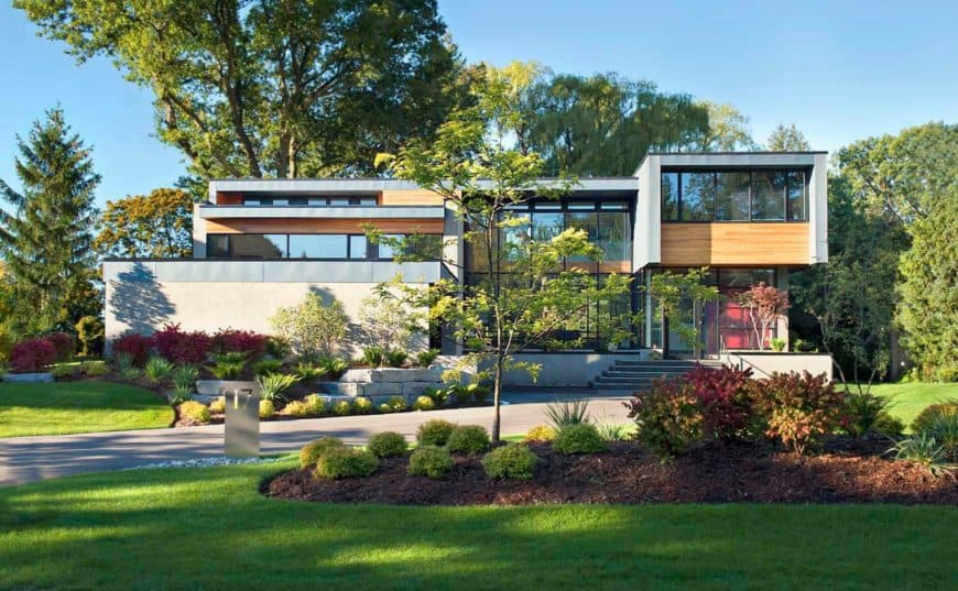Large modern house featuring a beautiful lawn and garden areas along with a dramatic driveway leading to the home's entry.