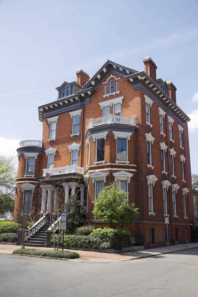 3-story red brick and a white trim Victorian mansion on corner lot in an urban setting.
