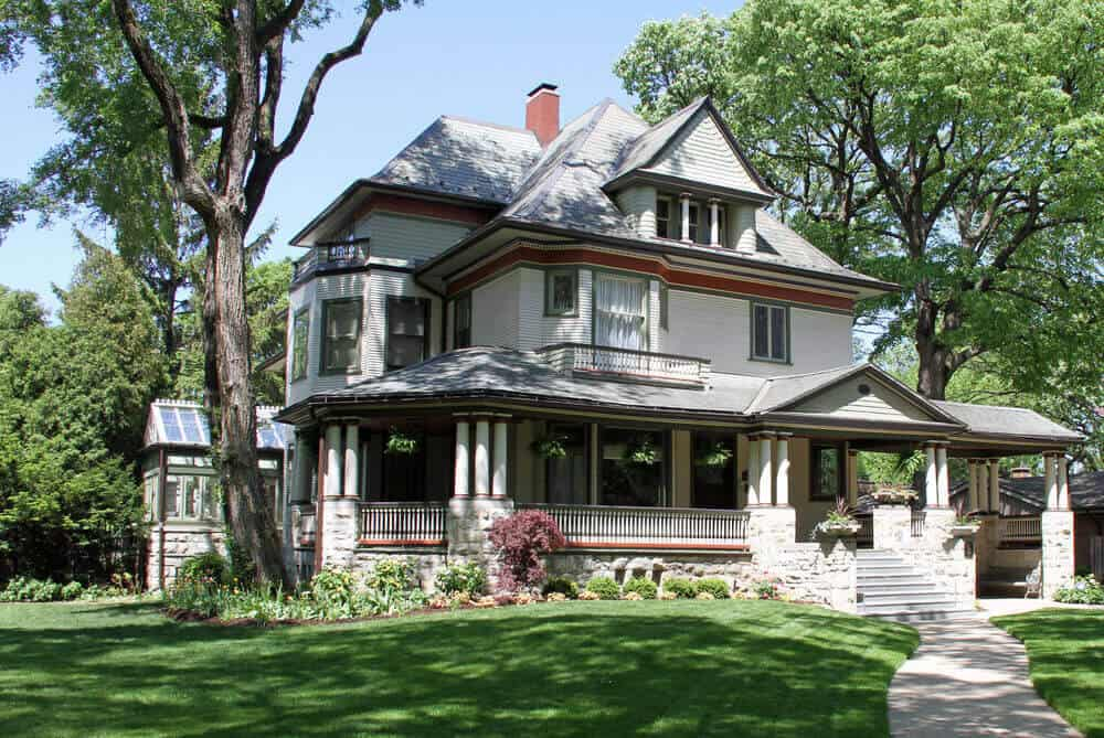 Modestly designed three-story Victorian home with full-width front porch and solarium in the back.