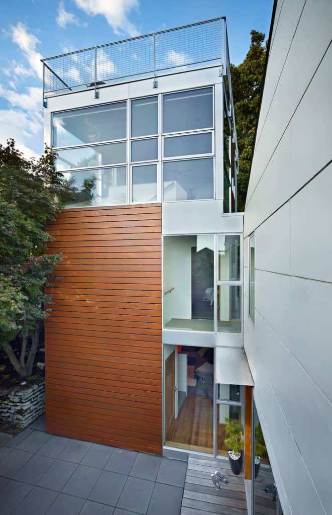 A modern tower house with glass windows and concrete backyard.