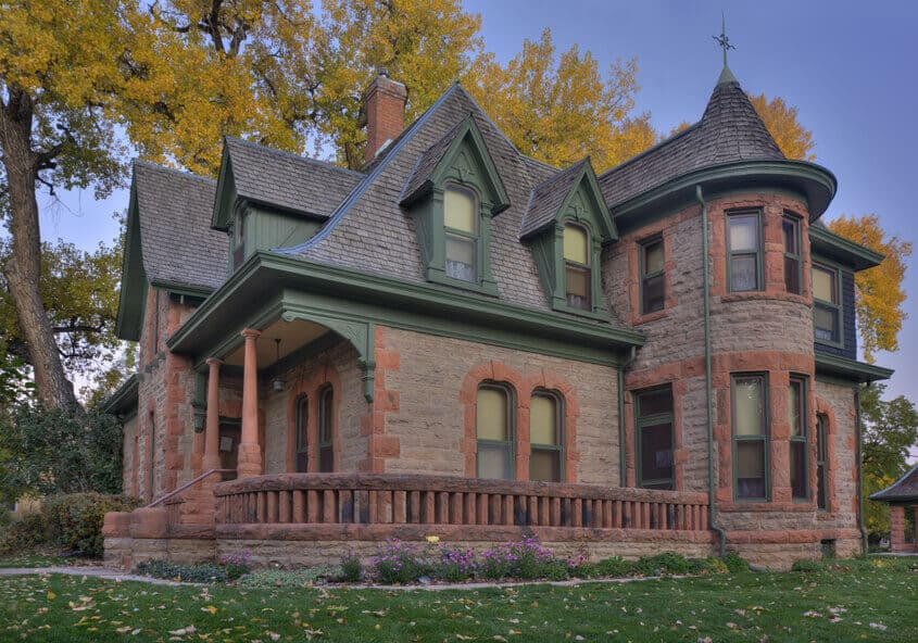 Brick Victorian home with front deck in Fort Collins, Colorado.