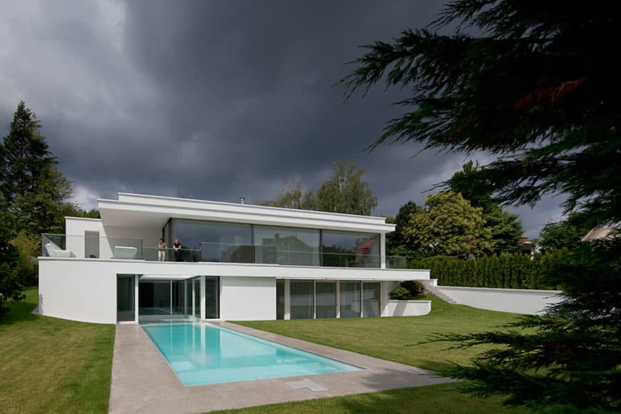 White modern house with a large backyard featuring a swimming pool and a well-maintained lawn area.