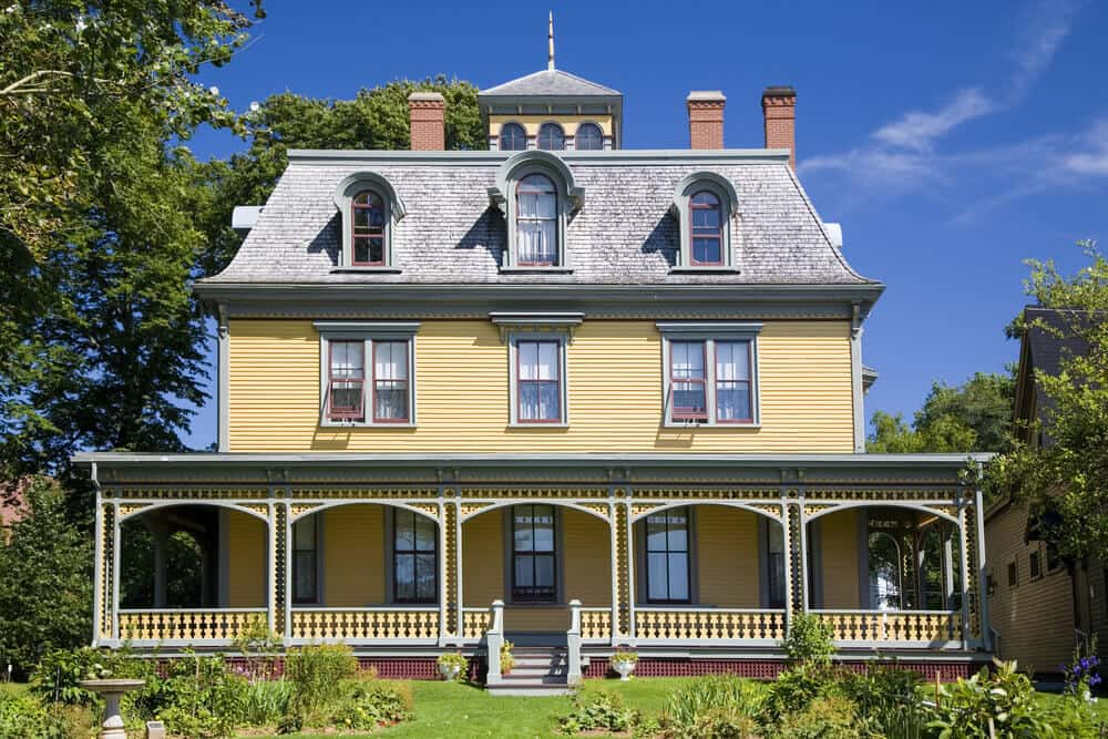 Victorian-inspired home in yellow with full-width front porch located in Prince Edward Island, Canada.