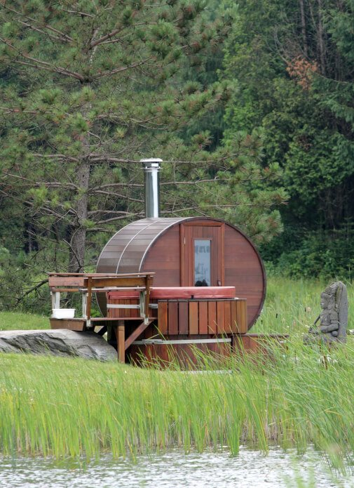 Traditional barrel sauna with deck on the edge of a lake