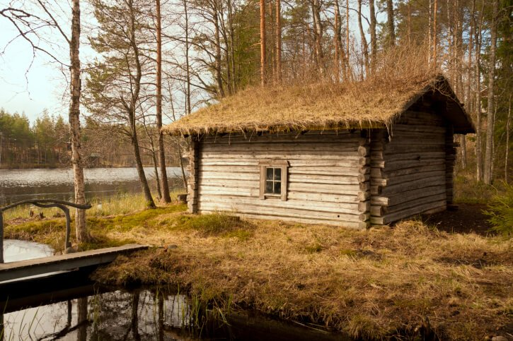 Old wooden sauna house on the edge of a lake