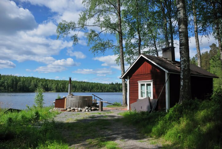 Red sauna hut typical of those found in Sweden and Finland build on the edge of a lake