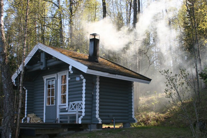 Very nicely built blue and white sauna hut in the forest