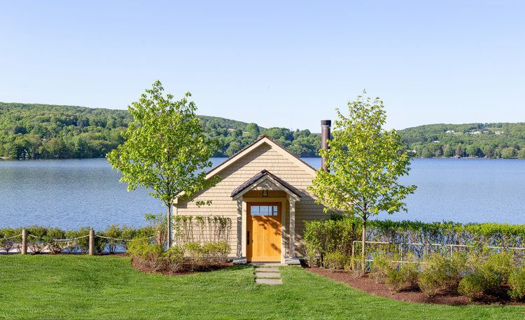 A small lake house featuring a wooden exterior and a sprawling lawn area. It also offers a breathtaking view of the lake.