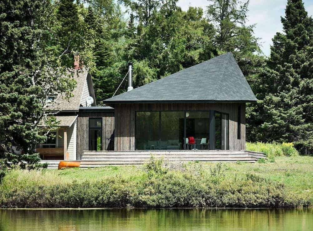 A stylish home by the lake with a wooden exterior and a black roof.