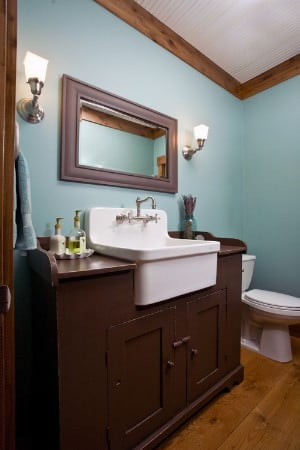 Small primary bathroom with farmhouse sink and hardwood flooring.