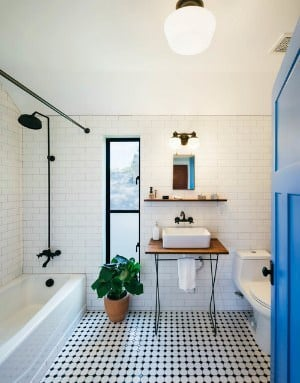 Remodelled bathroom with black and white floor and subway tile on all walls.