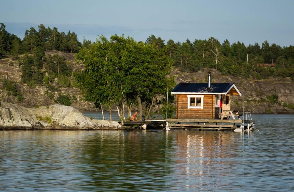 Sauna hut on dock floating on a lake