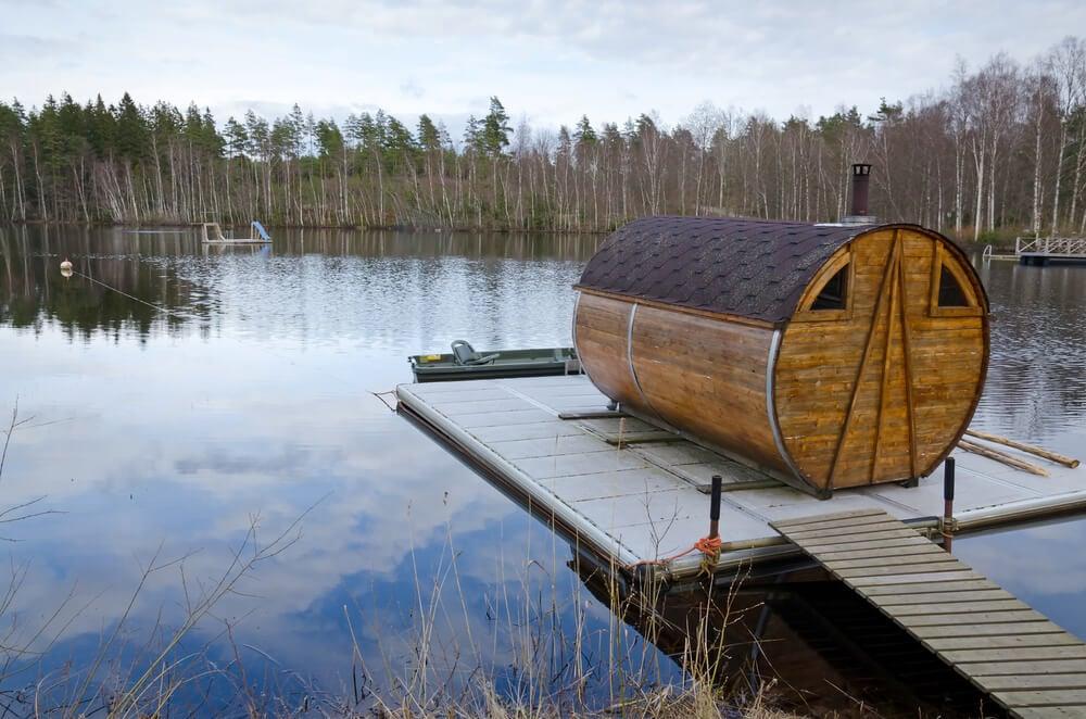 Barrel sauna on a floating dock on a lake