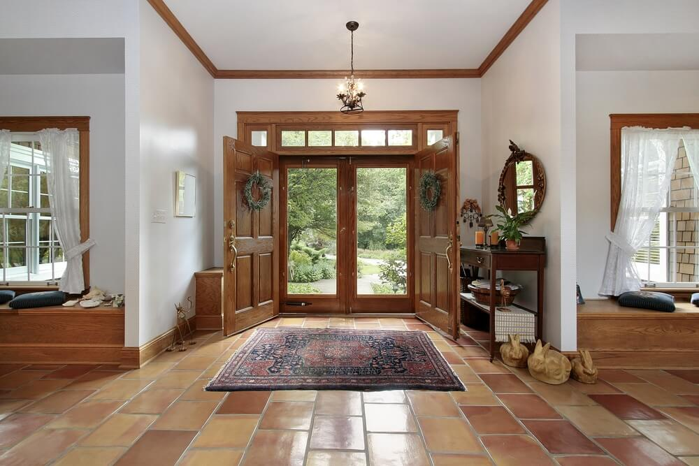 One-story foyer with brown tile floor opening up to the left and right of the home. Built in benches lie under the windows framing the front door and entrance hall.