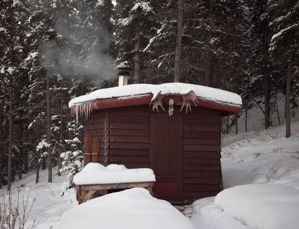 Small wood sauna hut in the snow