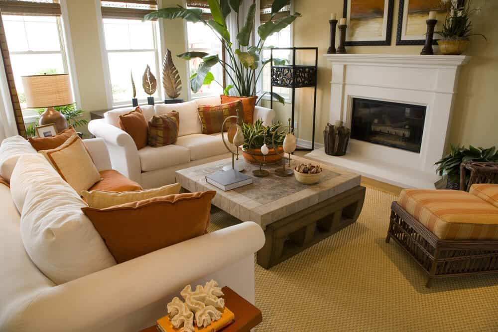 Bright and colorful living room design with off-white sofas decorated with orange and brown pillows. One wall of large windows flood the space with natural light.