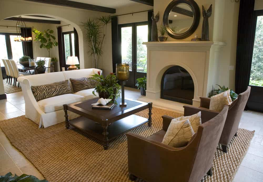 Open living area home with living room situated around an oval shaped gas fireplace. Living room is small in size but doesn't appear small due to the open concept living space.