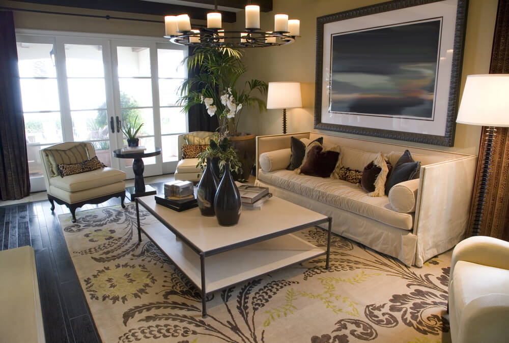 The coffee table is what sets this living room apart being a two-level white table with a dark steel frame. The room is situated on a beige, brown and green rug under which is dark wood flooring.