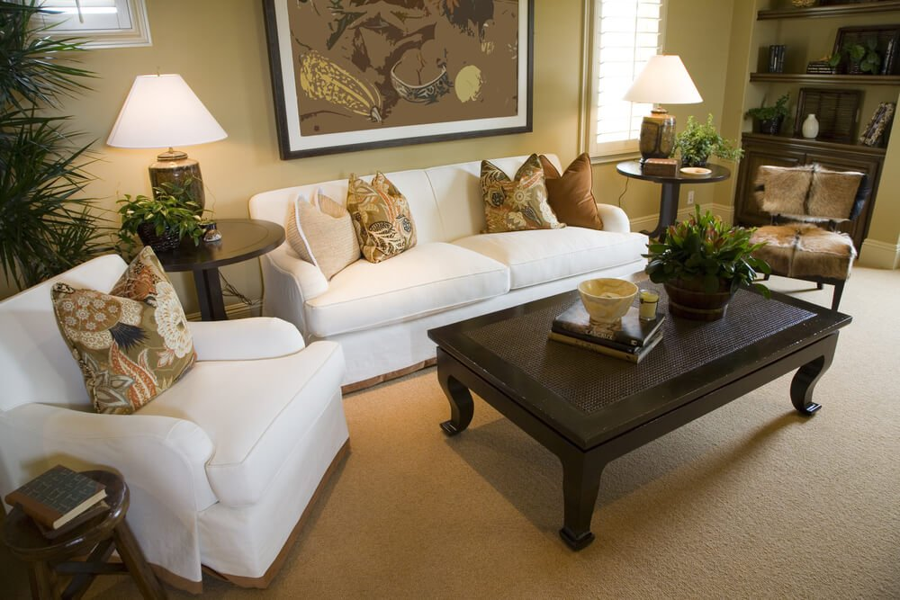 Simple living room with one small white sofa, one white armchair and one armless antique chair around a rectangular dark brown coffee table.
