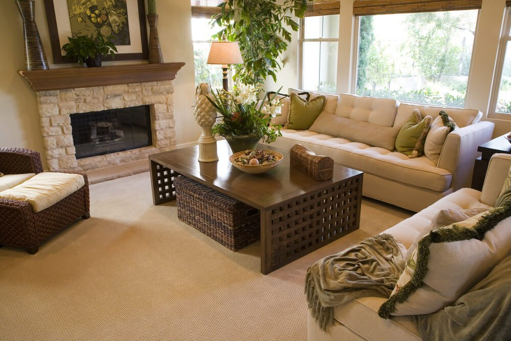 Beige dominant living room design with wood coffee table that has lattice design sides. Room includes dark brown wicker armchair and ottoman.