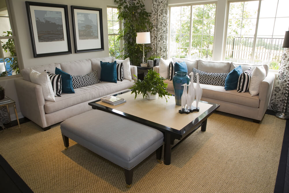 Cottage style living room with off-white sofas decorated with white and blue pillows. The coffee table has a dark brown frame with light brown top. Adjacent to the coffee table is a rectangular blue ottoman.