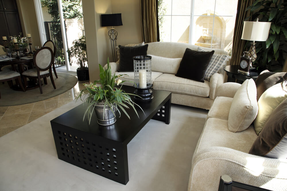 Light and dark living room design with off-white sofas and dark coffee table on an off-white area rug. Dark pillows on the sofas match the coffee table.