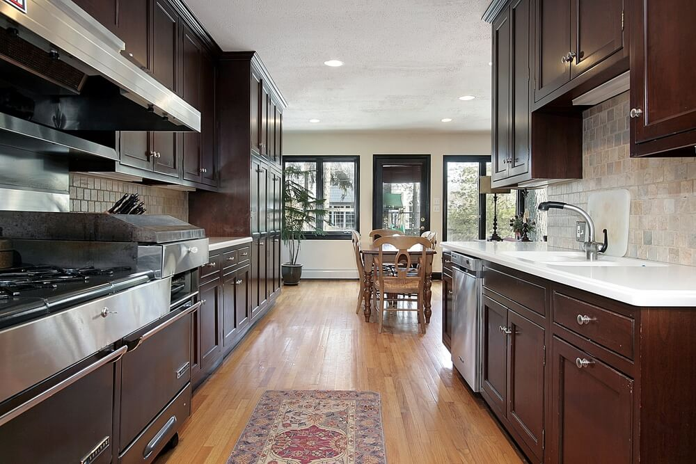Narrow cooking area opens into wide dining room in this kitchen featuring the familiar match of dark wood cabinetry and naturally lighter hardwood flooring.